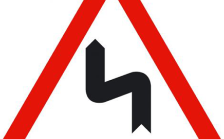 Señal vertical de advertencia de peligro por la proximidad de una sucesión de curvas hacia la izquierda