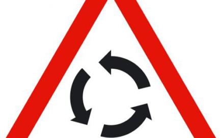 Señal vertical de advertencia de peligro en intersección con circulación giratoria