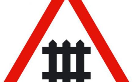 Señal vertical de advertencia de peligro por la proximidad de un paso a nivel con barreras
